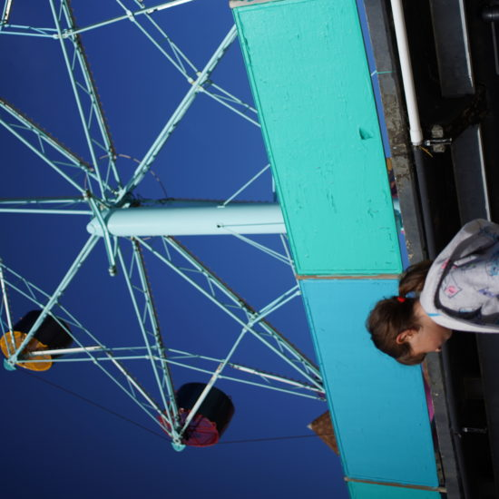 Girl standing below a ferris wheel on the Santa Cruz boardwalk