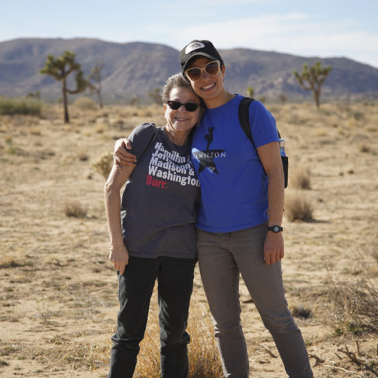 Taller adult daughter hugging mom in Joshua Tree State Park