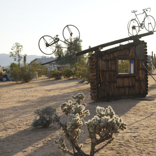 Photo of a sculpture in the desert with two bicycles on top of a small wood hut. Cactus in the forefront