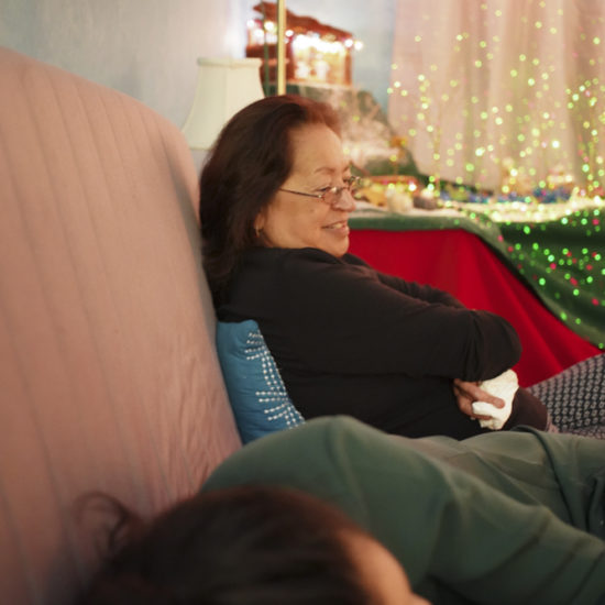 Mom looking over napping daughter on couch